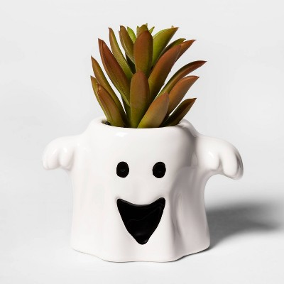 White ceramic planter that looks like a ghost, with a faux green succulent inside