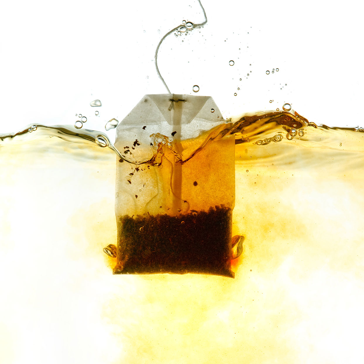 tea bag being dunked in water