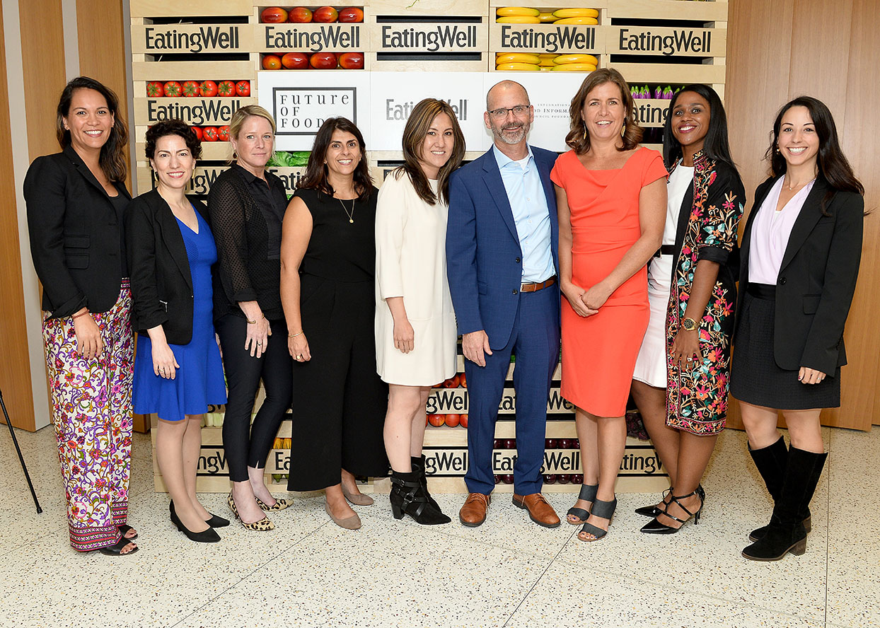 9 members of the EatingWell and IFIC staff celebrate an amazing future of food summit standing in front of fruit and vegetable backdrop