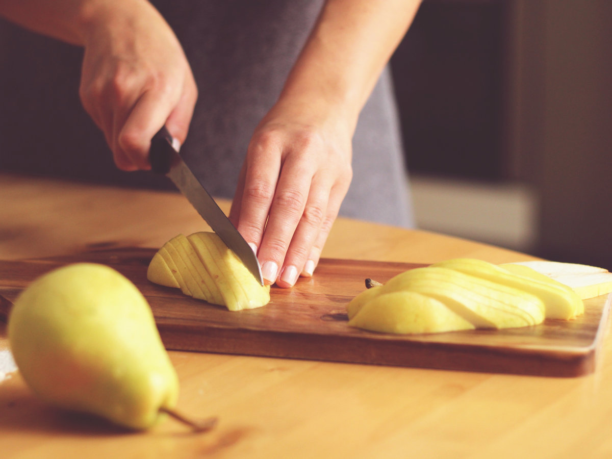 person slicing a pear into neat thin slices