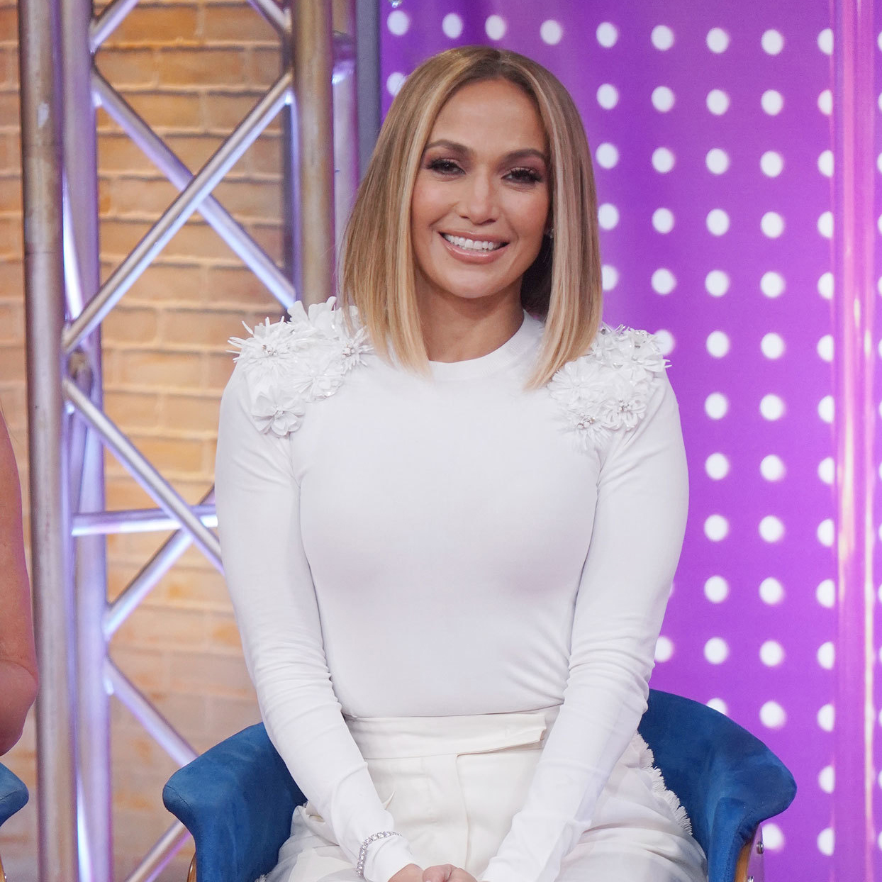 Jennifer Lopez in white outfit sitting on a colorful set
