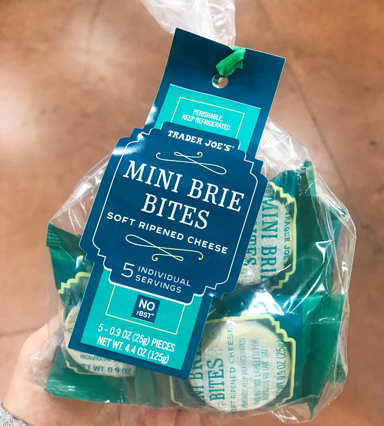hand holding mini brie bites from trader joe's