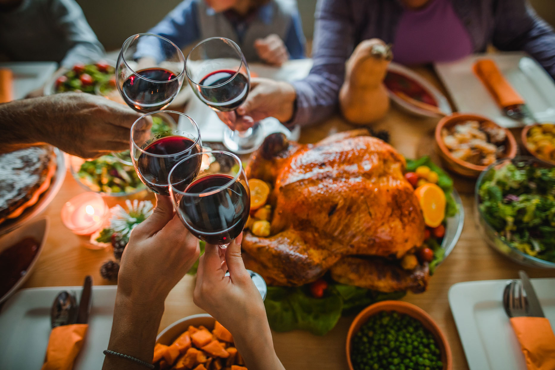 table set with Thanksgiving dinner with hands raising their wine glasses for a cheers