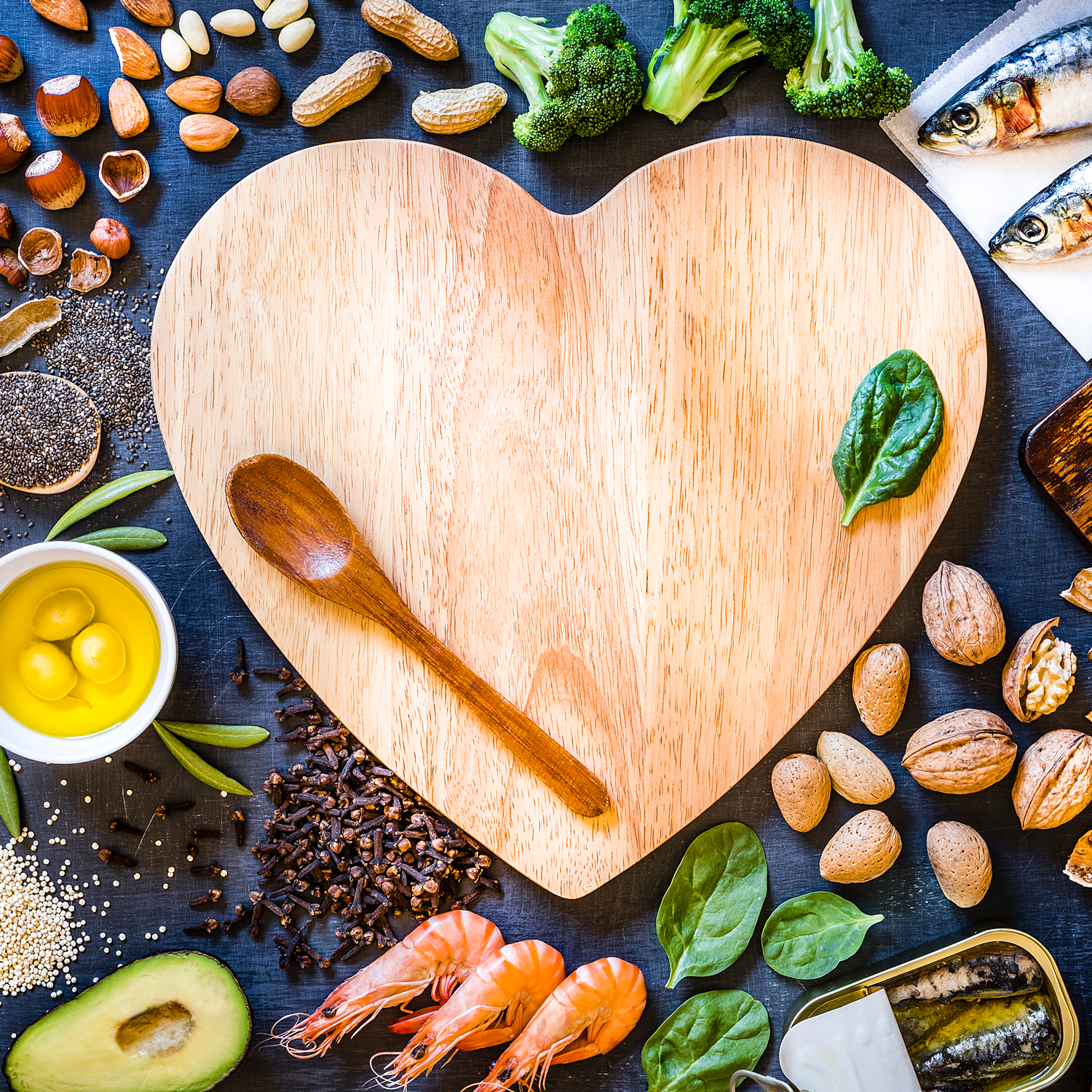 heart shaped cutting board with healthy foods surrounding it