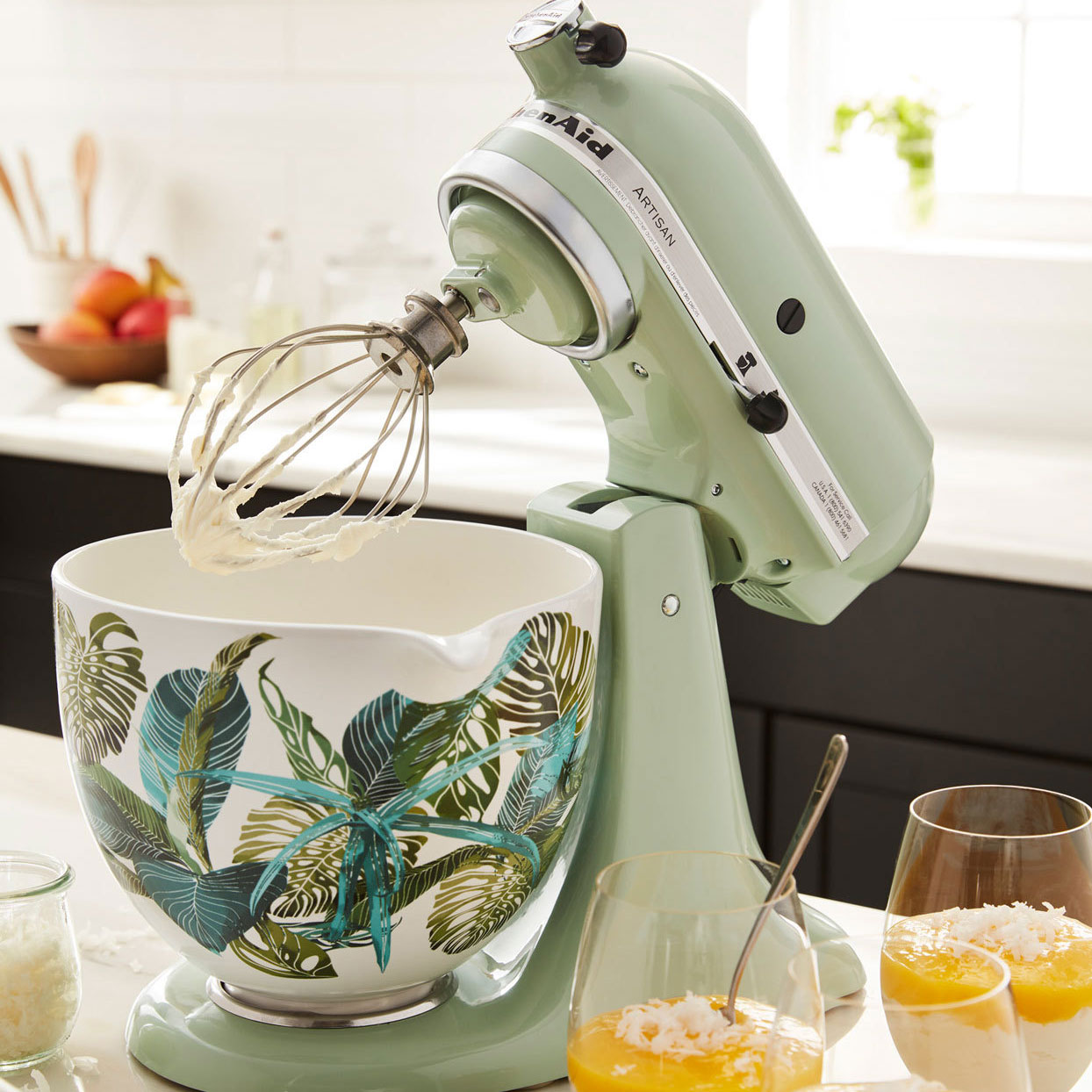 Pistachio colored KitchenAid mixer with decorative bowl with tropical leaves print on the outside