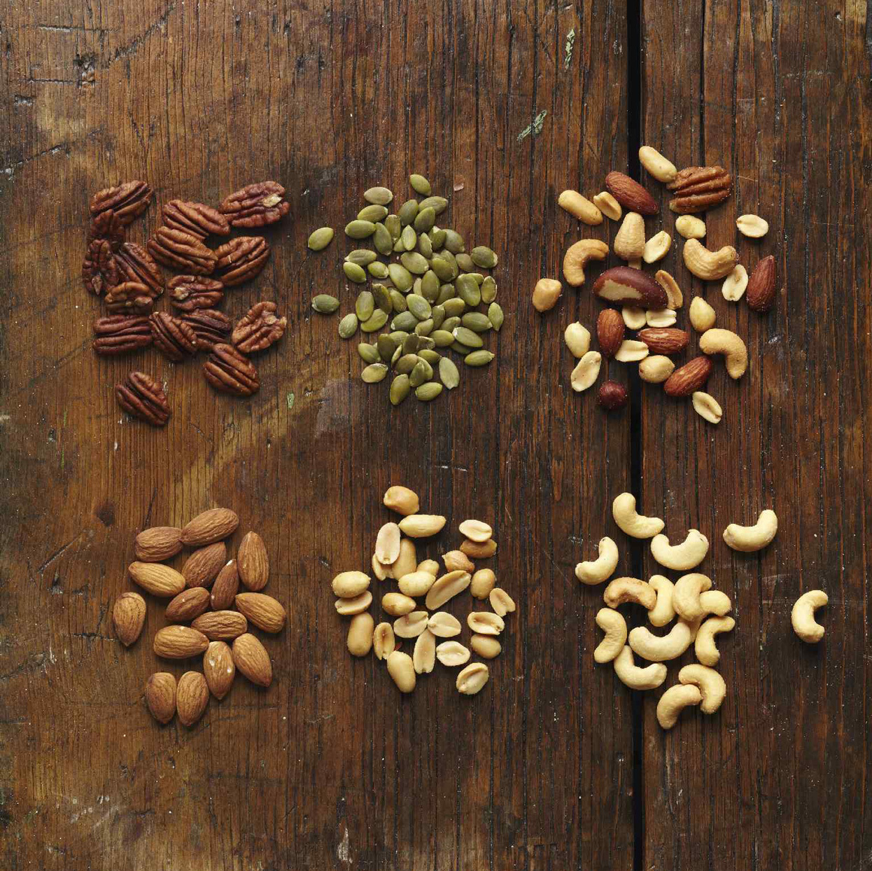 6 piles of different nuts, including almonds, peanuts and cashews, on wood background