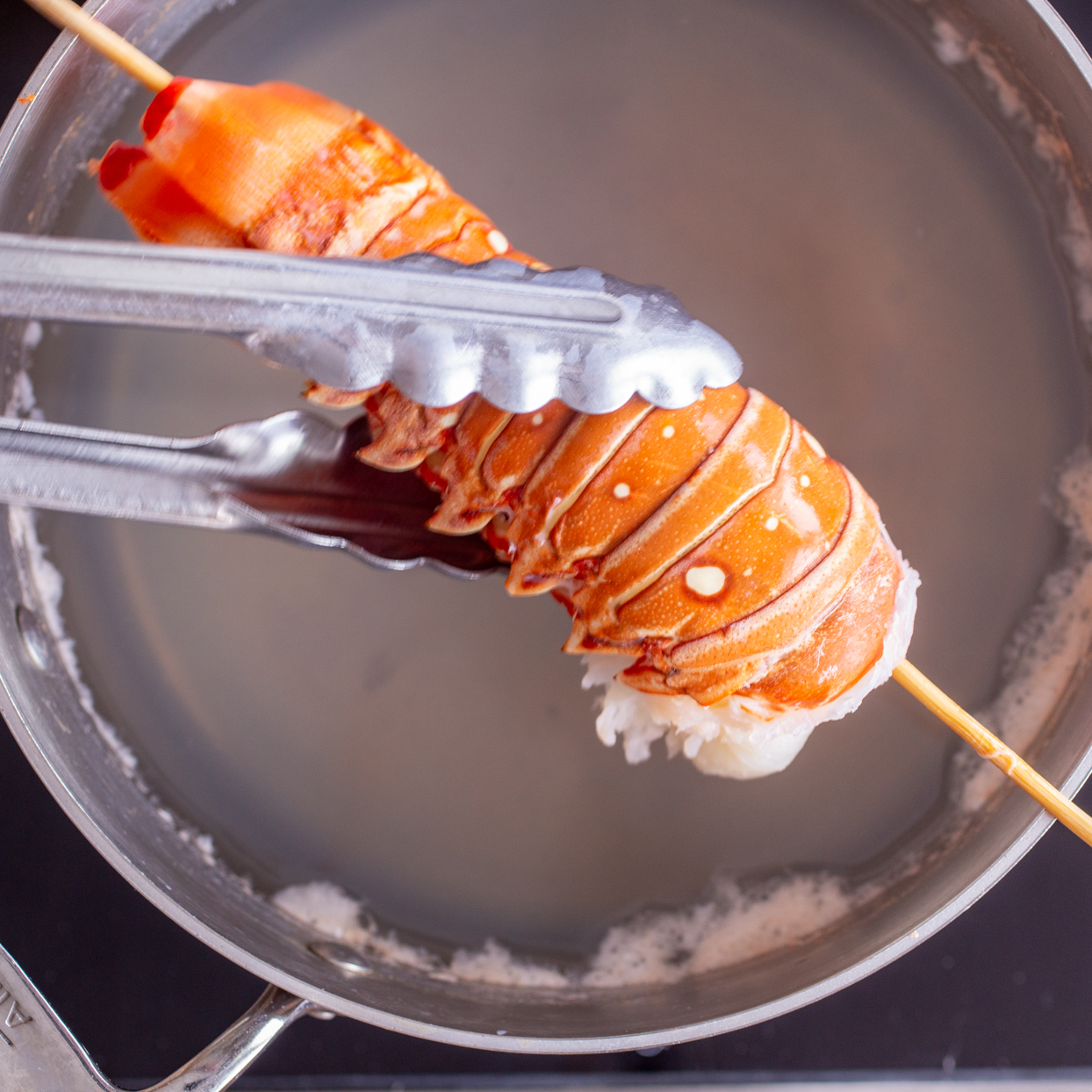 tongs removing a skewered lobster tail into a pot