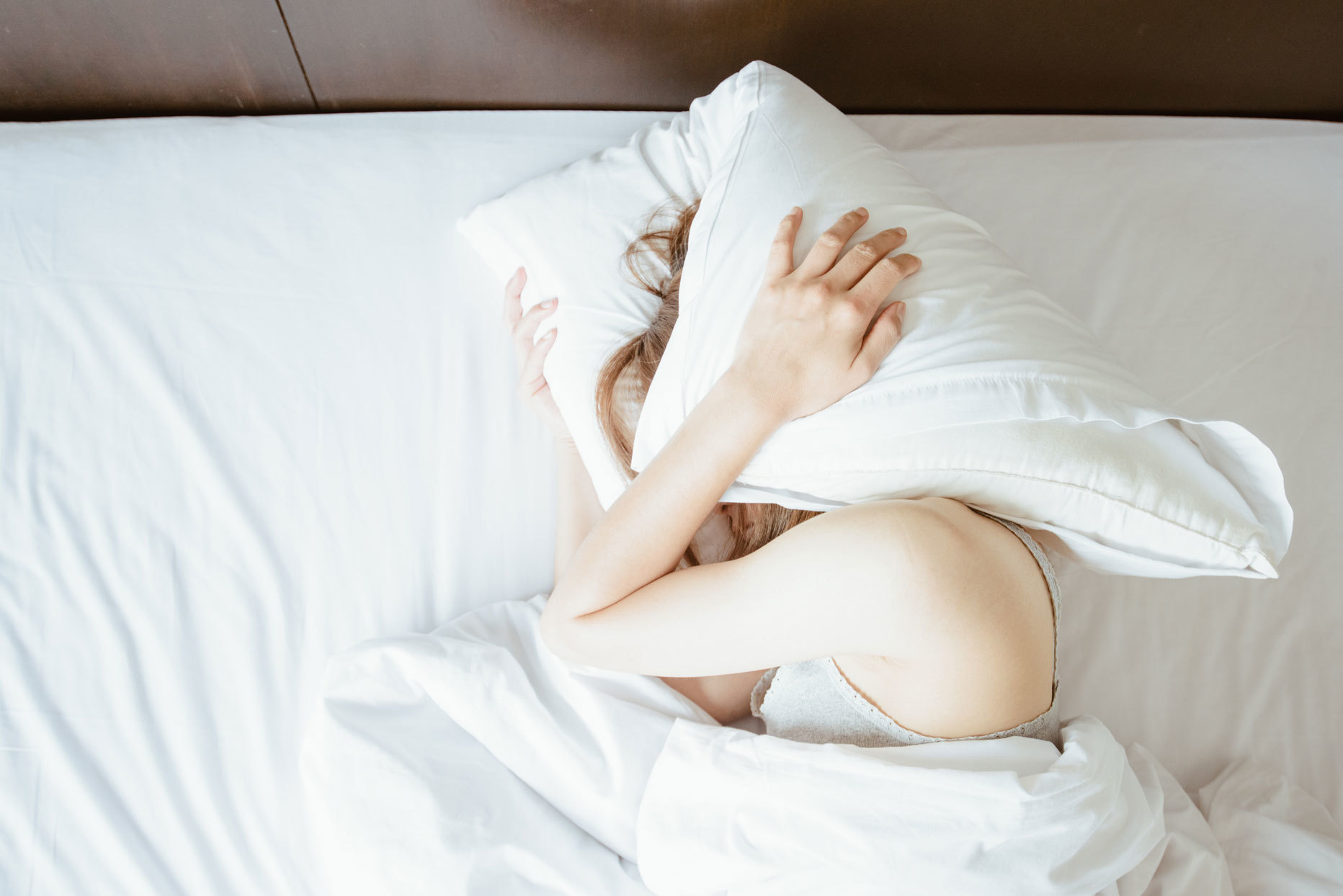 woman laying in bed and holding a pillow over her head
