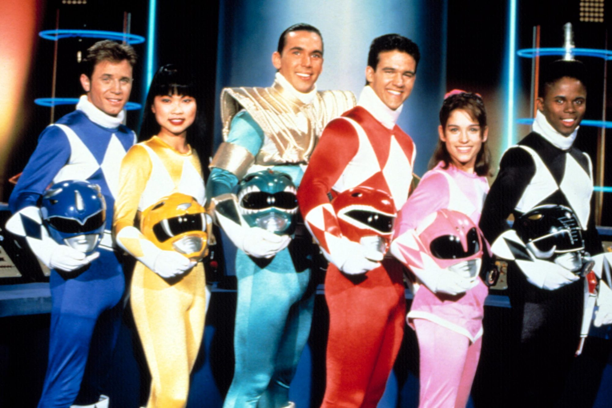 The original cast of the Mighty Morphin Power Rangers stand next to one another in their Power Ranger outfits. They each holds their helmets in their arms and smile at the camera.